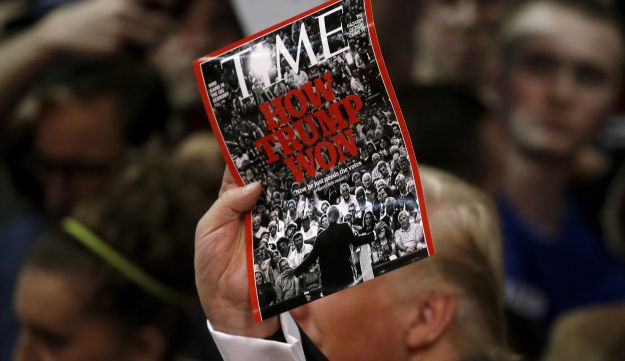 Trump holds up a Time Magazine cover following a campaign rally in Syracuse, New York, April 16, 2016.