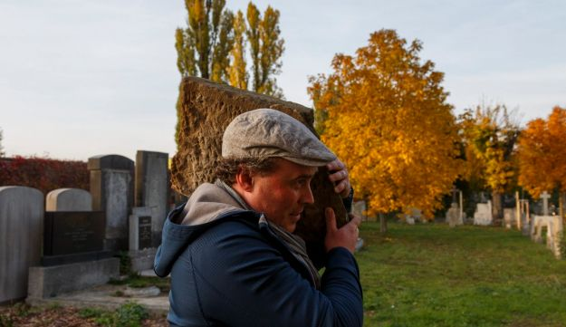 In this picture taken on Monday October 26, 2015, Tomas Jelinek carries a tombstone in efforts to restore a former Jewish cemetery in Prostejov, Czech Republic. A team of volunteers, led by Jelinek, is trying to restore the graveyard desecrated by Nazi's over 70 years ago. Some of its 2000 removed tombstones have been used for decades as construction materials while the graveyard itself now is a park where people walk their dogs.