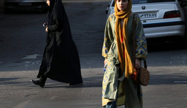 In this Thursday, Aug. 24, 2017, photo, two Iranian women make their way in a square while one of them wears the chador in downtown Tehran, Iran.