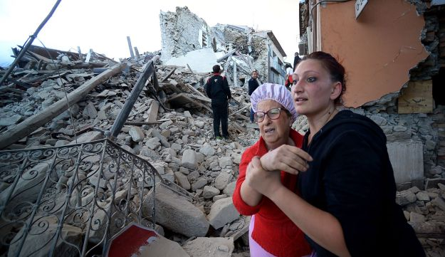 Residents reacts among the rubble after a strong earthquake hit Amatrice, Italy, August 24, 2016.