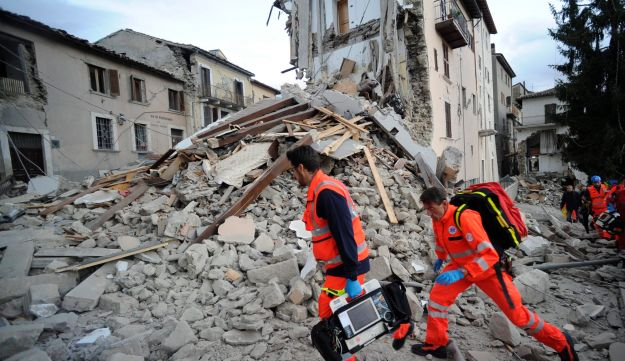 Rescuers search a crumbled building in Arcuata del Tronto after an earthquake struck, Italy, August 24, 2016.