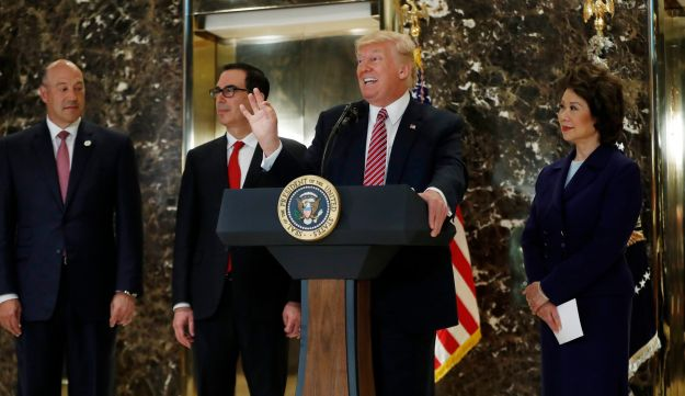 President Donald Trump, accompanied by, from left, National Economic Council Director Gary Cohn Treasury Secretary Steven Mnuchin and Transportation Secretary Elaine Chao, speaks to the media in the lobby of Trump Tower in New York, Tuesday, Aug. 15, 2017. (AP Photo/Pablo Martinez Monsivais)