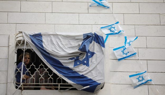 A Jewish settler youth looks out from a window covered with an Israeli flag hanging on a disputed building where about a hundred hard-line Jewish settlers have hunkered down, in the West Bank city of Hebron on July 26, 2017.