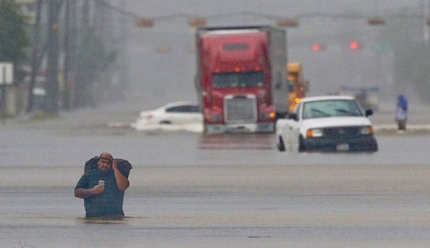 A man carries his belonging as he walks through the flooded waters on Telephone Rd. in Houston on August 27, 2017