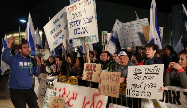 Protesters hold signs and chant at a demonstration against the government's natural gas plan in Tel Aviv on December 5, 2015.