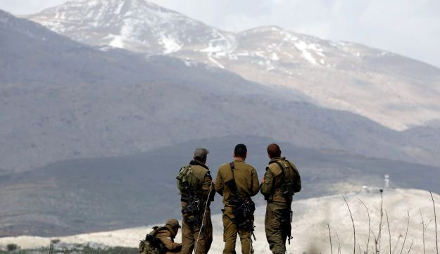 Israeli soldiers stand on a field overlooking Syria in the Golan Heights March 19, 2014