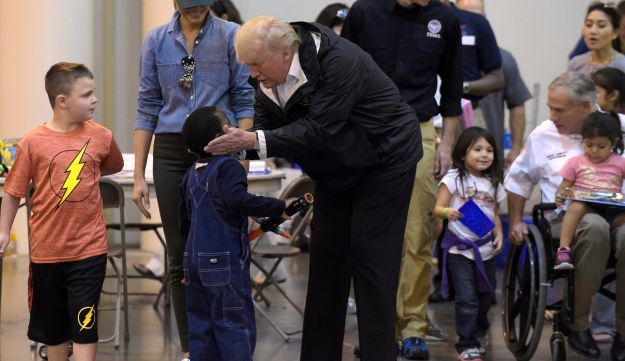 U.S. President Donald Trump, alongside wife Melania, cups the face of a boy impacted by Hurricane Harvey during a visit to the NRG Center in Houston, September 2, 2017.