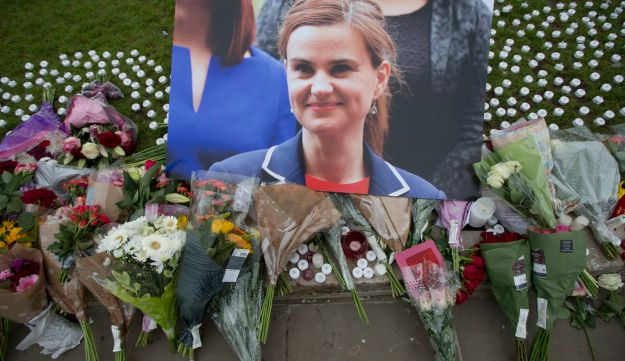 An image and floral tributes for MP Jo Cox outside the House of Parliament in London, June 2016. Cox was stabbed to death by Thomas Mair, who identified himself in court with a National Action slogan.