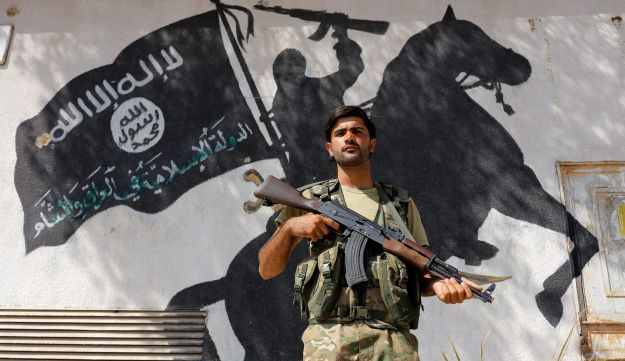 A member of Turkish-backed Free Syrian Army, seen with an ISIS mural in the background, stands guard in the border town of Jarablus, Syria, August 31, 2016.