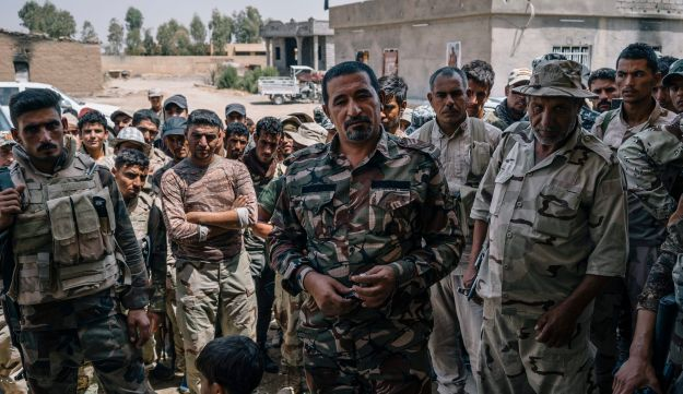 Sheikh Nazhan Sakhar speaks to his men holding an ISIS flag they captured in Hajj Ali, Iraq, August 9, 2016.