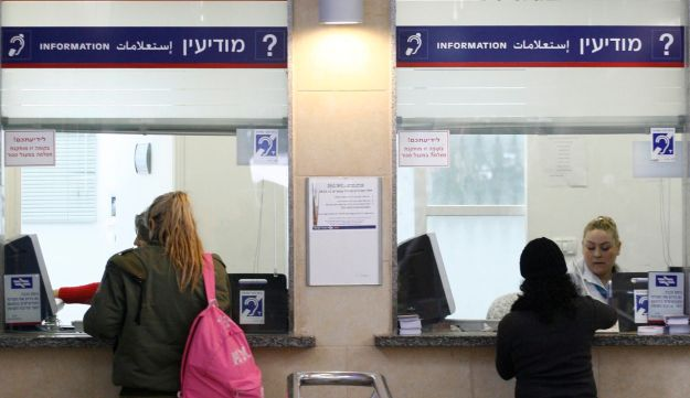 FILE PHOTO: Israeli soldier buys ticket at Tel Aviv train station.
