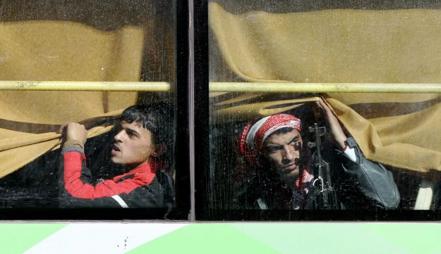 Syrian rebel fighters are seen on a bus as hundreds of civilians and rebel forces began evacuating the last opposition-held district under a deal with the Syrian regime, Homs, Syria, December 9, 2015.