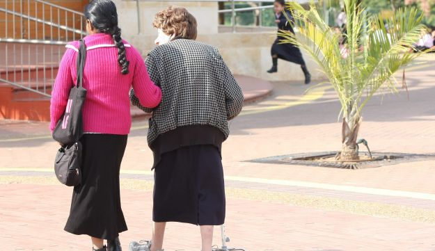 A foreign caregiver walks alongside an elderly lady in Ra'anana.