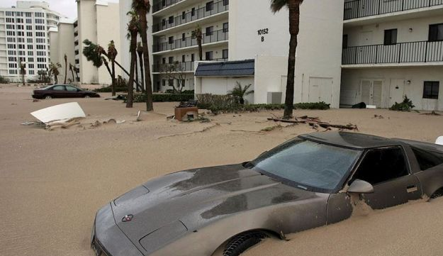 A Corvette sits in a parking lot, covered with sand from Hurricane Jeanne's storm surge, outside the Ocean Rise condos on Hutchinson Island, Fla., Sunday, Sept. 26, 2004