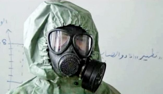 A screengrab of an AP video from Sept. 18, 2013 shows a student wearing a gas mask and protective suit during a session on reacting to a chemical weapons attack, in Aleppo, Syria.