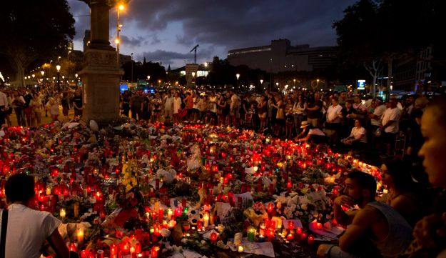 People stand next to candles and flowers placed on the ground, after a terror attack claimed by ISIS that killed at least 14 people and wounded over 120 in Barcelona, Spain. Aug. 20, 2017