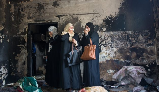 File photo: Three women stand inside the Dawabsheh family home in Duma, West Bank, where an arson attack claimed three lives, August 4, 2015.