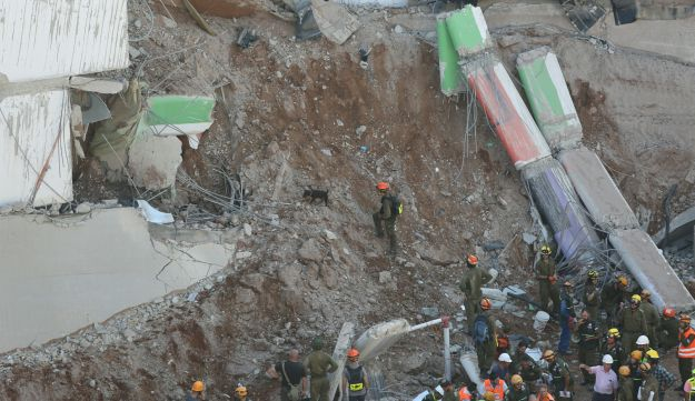 Rescue workers from the Home Front Command at the site of the collapsed multi-level parking garage under construction in Tel Aviv.