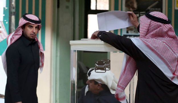 A Saudi man, center, casts his vote at a polling center during the country's municipal elections in Riyadh, Saudi Arabia, Dec. 12, 2015.