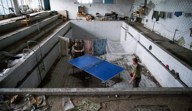In this photo taken on Thursday, Aug. 25, 2016, Ukrainian soldiers play table tennis at a damaged swimming pool in the village of Marinka, near Donetsk, eastern Ukraine.