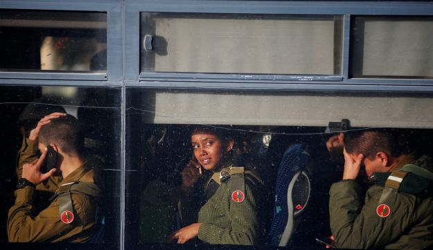 Israeli soldiers sit in a bus as they leave the scene of a truck-ramming attack in Jerusalem, January 8, 2017.