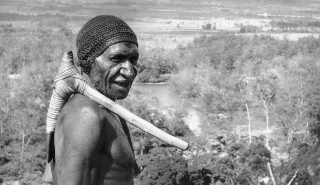 Warrior with stone axe on his shoulder, at the central mountain range of Papua New Guinea, February 20, 1962