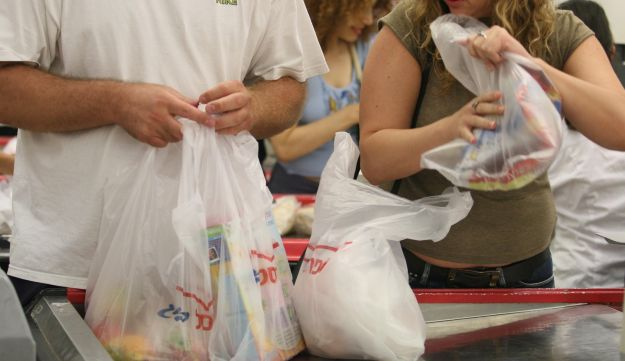 Israelis wrapping their shopping in plastic bags at a Shufersal supermarket. Picture shows a man in a white shirt with three bags, one clearly containing fresh produce and one a box of breakfast cereal. The third bag appears to have been doubled, presumably for strength. A woman standing next to him in line, wearing a brownish-greenish shirt and jeans, is holding a plastic bag with unclear content.
