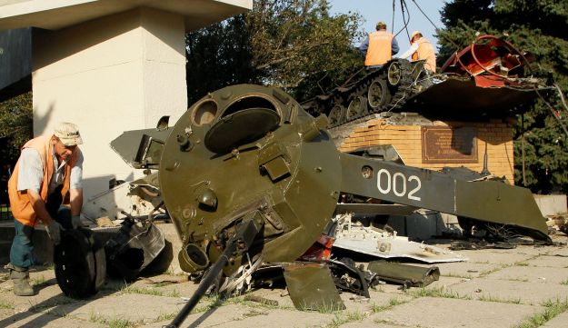 Workers remove a damaged airborne assault vehicle, a monument to perished paratroopers, at the site of a blast in the rebel-held city of Luhansk, Ukraine, September 19, 2017.