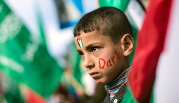 A Palestinian boy takes part in a protest against ongoing electricity shortages, with the Palestinian flag painted on his forehead, in Gaza City on January 10,
