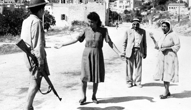 An Israeli soldier, armed with a rifle, stop some Arabs in a street in Nazareth, Palestine, July 17, 1948, as they are travelling after the allotted curfew time. Israeli forces had occupied the town earlier that day.