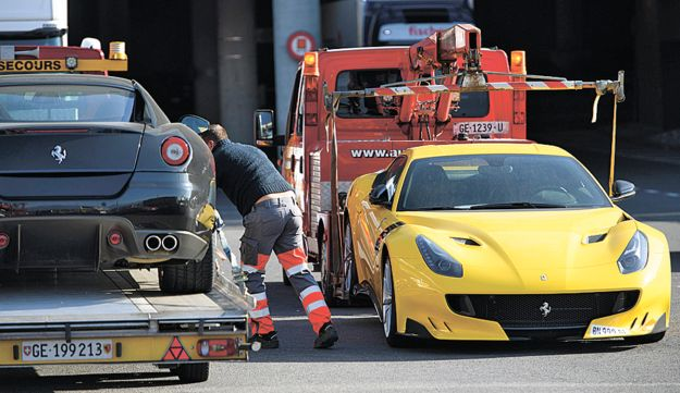 Two Ferrari sports cars are being towed off the freight zone by the police at Geneva Airport, in Geneva, Switzerland, on Thursday, Nov.3  2016. Geneva authorities have confiscated 11 luxury vehicles and sports cars Monday,  belonging to Teodorin Obiang Nguema,, the son of Equatorial Guinea's president as part of a preliminary investigation into alleged corruption.  (Laurent Gillieron/Keystone via AP)