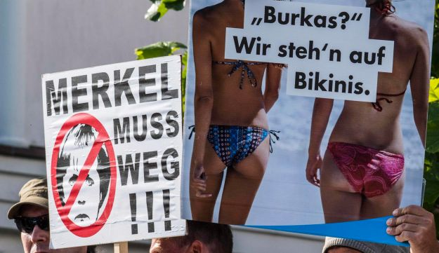 Members of the far-right Alternative for Germany (AfD) displaying placards as German Chancellor Angela Merkel (unseen) arrived for an election rally in Binz, September 16, 2017.