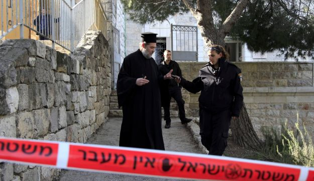 A Greek Orthodox priest talking to an Israeli policewoman outside a seminary in Jerusalem, February 2015. The seminary was damaged by fire and anti-Christian slogans were written in Hebrew, in what Israeli police said they suspect was a hate crime.