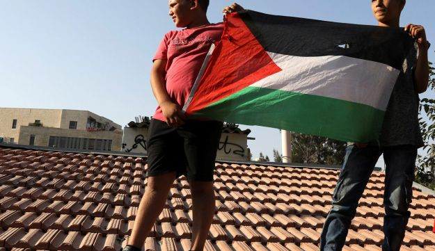 Palestinian boys hold a flag during a protest against a Jewish settlement in the Sheikh Jarrah neighborhood in East Jerusalem. September 8, 2017
