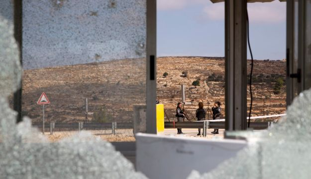 Israeli security officers are seen through bullets shattered windows of the check point at the entrance to Har Adar settlement near Jerusalem, Tuesday, Sept. 26, 2017. Israeli police said that a Palestinian attacker opened fire at the entrance to the settlement killing three Israeli men and critically wounding a fourth.