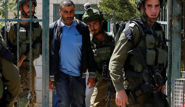 Israeli soldiers arrest the brother of Palestinian gunman Nimr Jamal near the West Bank City of Ramallah September 26, 2017.