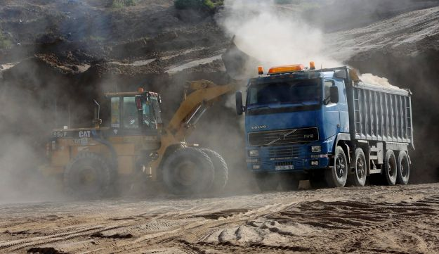 In this Tuesday, Sept. 26, 2017 photo, a bulldozer removes sand at Tel Es-Sakan hill, south of Gaza City.