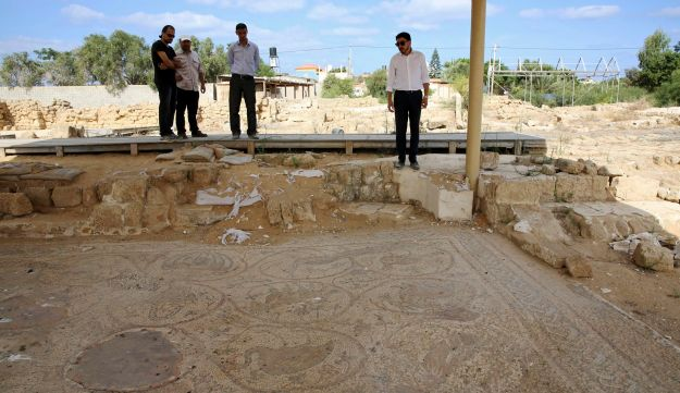 In this Tuesday, Sept. 26, 2017 photo, Junaid Sorosh-Wali, right, a UNESCO official, inspects the remains of a mosaic at St. Hilarion monastery, a site of early Christianity, in Nusseirat, central Gaza Strip. Gaza is home to numerous ancient treasures, but politics have long complicated archaeological work. At the monastery, which spans from the late Roman Empire to the Islamic Umayyad period, a breach in the fence suggested looters were trying to get in. (AP Photo/Adel Hana)