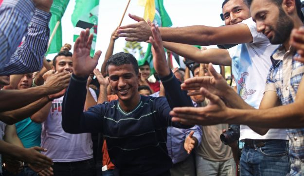 Palestinians celebrate after rival factions Hamas and Fatah reached an agreement on ending a decade-long split, Gaza City, Gaza, October 12, 2017.