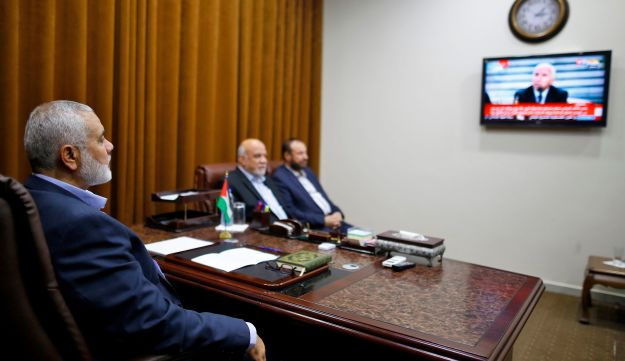 Hamas chief Ismail Haniya watches coverage of reconciliation deal on October 12, 2017, at his office in Gaza City. Rival Palestinian factions Hamas and Fatah have reached agreement on aspects of their reconciliation bid during talks mediated by Egypt in Cairo this week, Hamas said on Thursday. / AFP PHOTO / MOHAMMED ABED