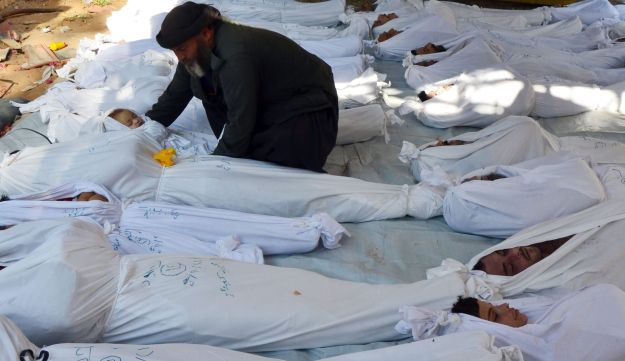 A man holds the body of a dead child among bodies of people activists say were killed by nerve gas in the Ghouta region outside of Damascus, Syria, August 21, 2013.