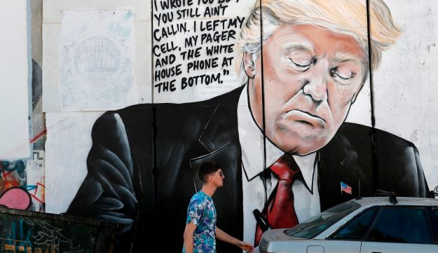 A man walks past a new piece of graffiti depicting US President Donald Trump on the controversial Israeli separation barrier separating the West Bank town of Bethlehem from Jerusalem on October 15, 2017.