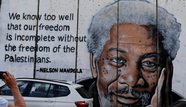 A man takes pictures of a mural on the Israeli wall depicting actor Morgan Freeman accompanied by a quote by Nelson Mandela in the West Bank city of Bethlehem, October 16, 2017.