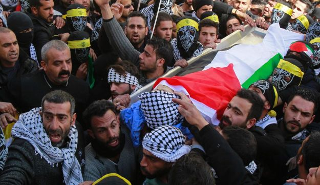 Mourners carry the body of Qusai Al Amour at his funeral in the West Bank village of Tuqu, January 17, 2017.
