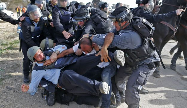 Israeli policemen detain a Bedouin man during clashes that followed a protest against home demolitions on January 18, 2017 in the Bedouin village of Umm al-Hiran, which is not recognized by the Israeli government, near the southern city of Beersheba, in the Negev desert. An Israeli policeman was killed while taking part in an operation to demolish homes in the Bedouin village, with authorities claiming he was targeted in a car-ramming attack. The driver was earlier reported shot dead by police as residents disputed the police version of events, saying the driver was heading to the scene to talk with authorities in an attempt to halt the demolitions.