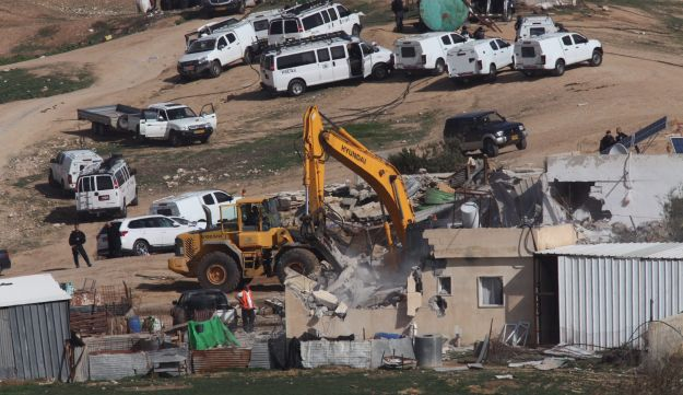 Israeli policemen stand guard as bulldozers demolish homes in the Bedouin village of Umm al-Hiran, which is not recognized by the Israeli government, near the southern city of Beersheba, in the Negev desert, on January 18, 2017.