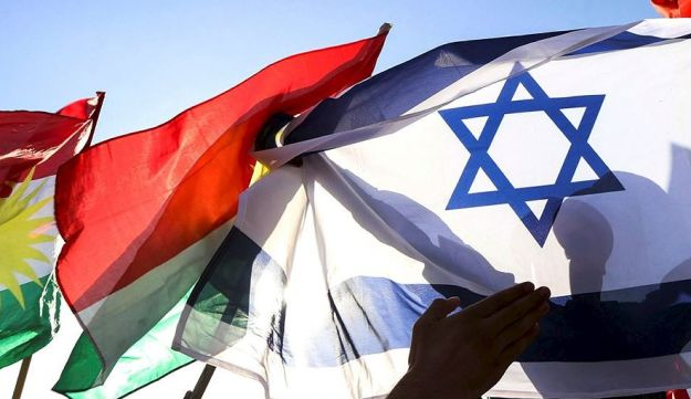 A picture taken on October 21, 2017 shows a man holding the Israeli flag as others raise the flag of Iraqi Kurdistan during a demonstration outside the UN Office in Arbil, the capital of the autonomous region, protesting against the escalating crisis with Baghdad