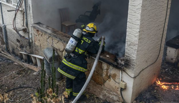 A firefighter works at the scene of a fire in Haifa on November 24, 2016.