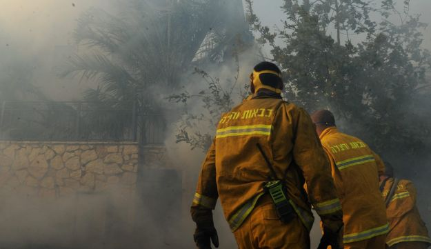 Firefighters extinguish the flames at a Zichron Yaakov home on November 23, 2016.
