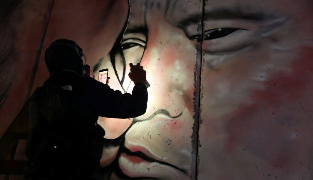 An Australian graffiti artist works on his mural depicting U.S. President Donald Trump and Israeli Prime Minister Benjamin Netanyahu on the controversial Israeli barrier in the West Bank city of Bethlehem October 28, 2017. Picture taken October 28, 2017.